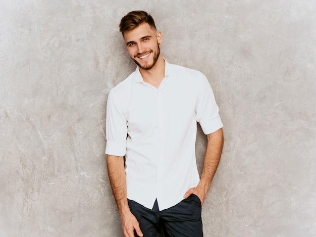 Portret van knap het glimlachen hipster zakenmanmodel die toevallig de zomer wit overhemd dragen. Gratis Foto