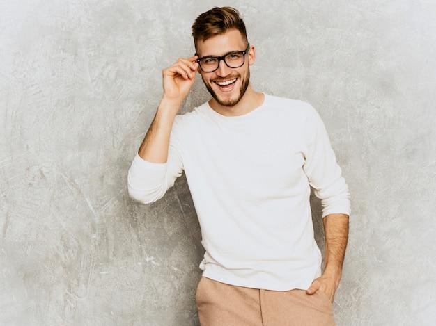 Portret van knap het glimlachen hipster zakenmanmodel die toevallige de zomer witte kleren dragen. Gratis Foto