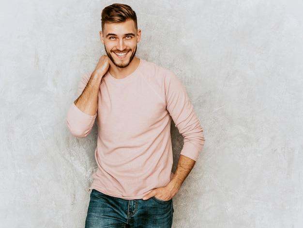 Portret van knap het glimlachen jonge mensenmodel die toevallige de zomer roze kleren dragen. mode stijlvolle man die zich voordeed Gratis Foto