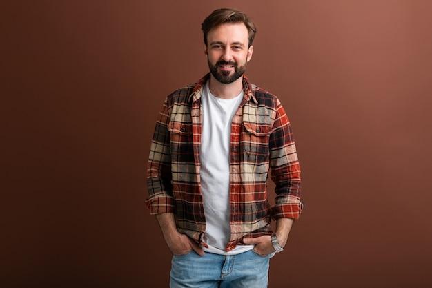 Portret van knappe aantrekkelijke stijlvolle bebaarde man op bruin Gratis Foto