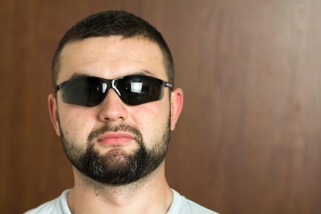 Portret van knappe bebaarde zwartharige intelligente moderne jongeman in glazen met kort kapsel en vriendelijke zwarte ogen glimlachend op onscherpe achtergrond. jeugd en vertrouwen concept. Premium Foto