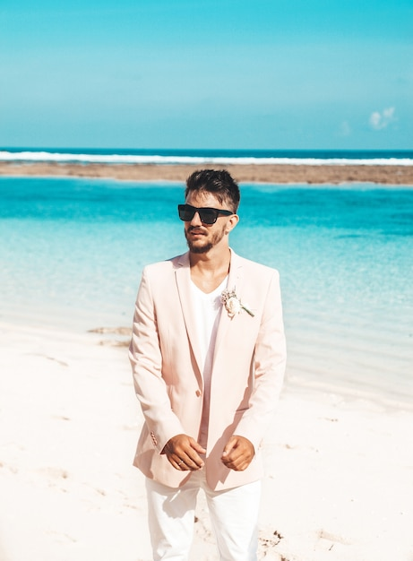 Portret van knappe bruidegom in het roze kostuum stellen op het strand achter blauwe hemel en oceaan Gratis Foto