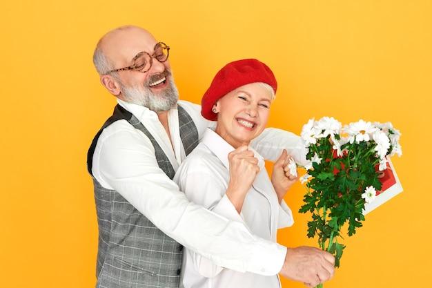 Portret van knappe charismatische senior man met kaalheid en grijze baard omarmen zijn mooie vrouw in rode baret Gratis Foto