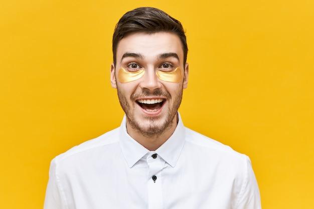 Portret van knappe energieke jonge mannelijke kantoormedewerker met opgewonden gezichtsuitdrukking die onder ooglapjes draagt om wallen, tekenen van vermoeidheid en stress te verminderen, zijn mond wijd openhoudend Gratis Foto
