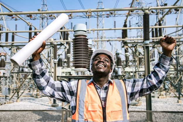 Portret van knappe engineering man met papieren plan voor check werkplek op de site en veiligheidshelm dragen voor high power power plant. achteraanzicht van aannemer op achtergrond van moderne energieopbouw. Premium Foto