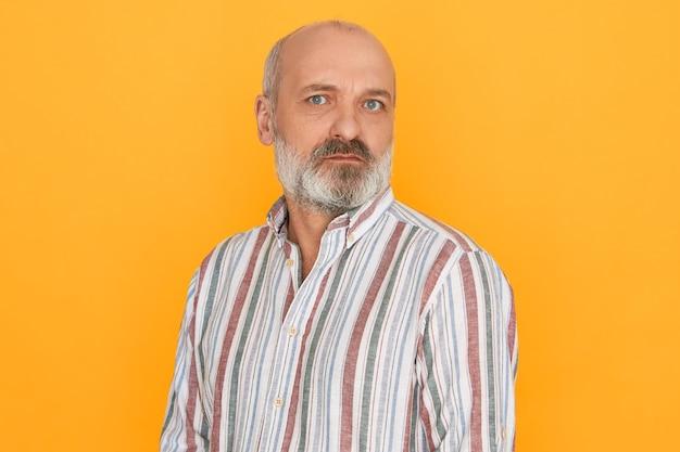 Portret van knappe europese mannelijke gepensioneerde m / v met kaal hoofd en dikke grijze baard kijken camera met twijfelachtige verdachte gezichtsuitdrukking, u niet vertrouwen. menselijke emoties en reactie Gratis Foto