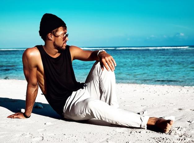 Portret van knappe hipster zonovergoten fashion man model dragen casual kleding in zwart t-shirt en zonnebril zittend op wit zand in de buurt van blauwe oceaan en lucht Gratis Foto