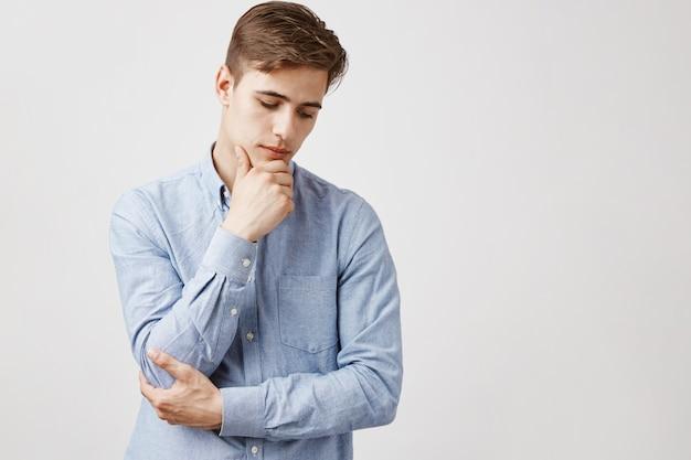 Portret van knappe jonge man met hand op kin, doordachte blik Gratis Foto
