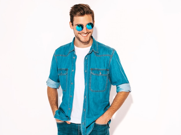 Portret van knappe lachende stijlvolle jonge man model dragen jeans kleding en zonnebril. mode man Gratis Foto
