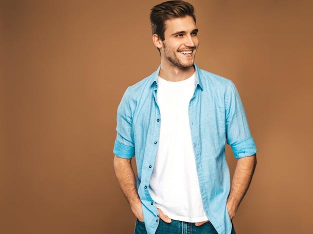 Portret van knappe lachende stijlvolle jonge man model gekleed in blauwe shirt kleding. mode man die zich voordeed Gratis Foto