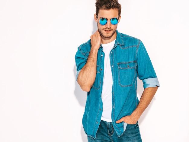 Portret van knappe lachende stijlvolle jonge man model gekleed in jeans kleding en zonnebril. mode man Gratis Foto