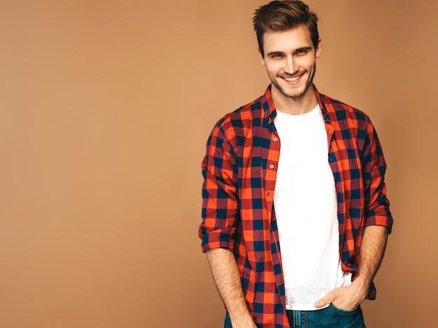 Portret van knappe lachende stijlvolle jonge man model gekleed in rood geruit hemd. mode man die zich voordeed Gratis Foto