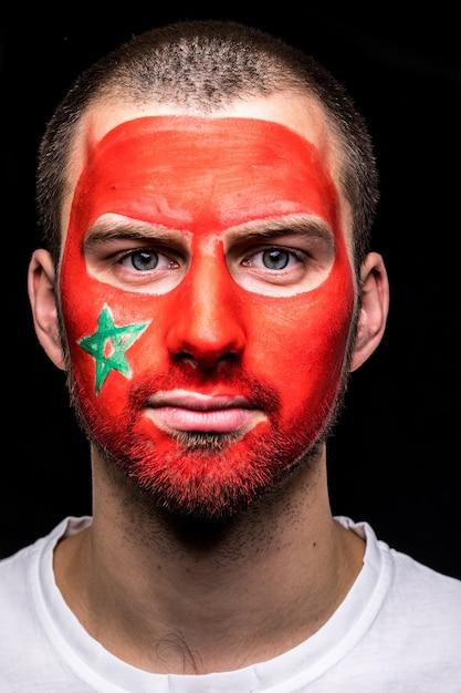 Portret van knappe man gezicht supporter fan van marokko nationale ploeg met geschilderde vlag gezicht geïsoleerd op zwarte achtergrond. fans van emoties. Gratis Foto