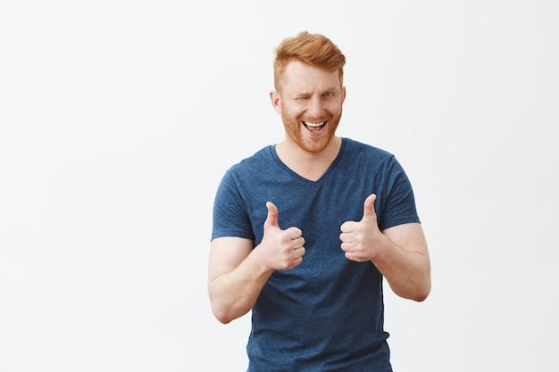 Portret van knappe man met rood haar duimen opdagen en knipogen met hint, leuk vinden en ondersteunen van grote beslissing, juichen over grijze muur Gratis Foto