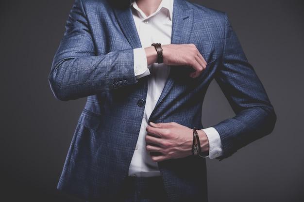 Portret van knappe mode stijlvolle hipster zakenman model gekleed in elegant blauw pak op grijs Gratis Foto