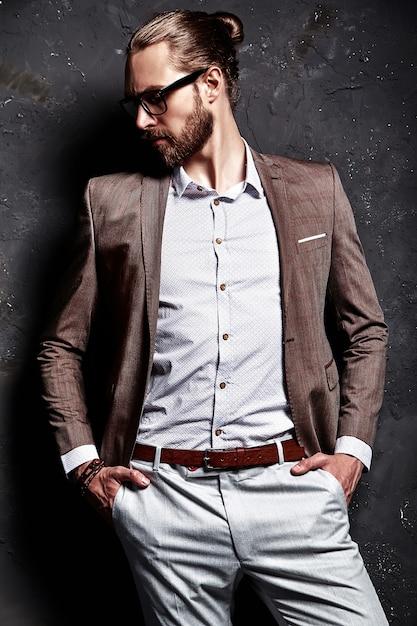 Portret van knappe mode stijlvolle hipster zakenman model gekleed in elegant bruin pak in glazen in de buurt van donkere muur Gratis Foto