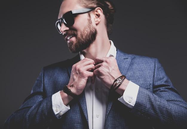 Portret van knappe mode stijlvolle hipster zakenman model gekleed in elegante blauwe pak poseren op grijs Gratis Foto
