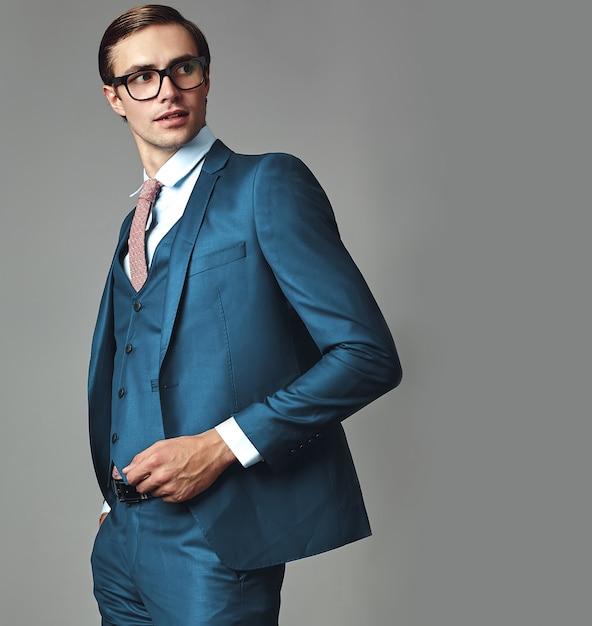 Portret van knappe mode stijlvolle hipster zakenman model gekleed in elegante blauwe pak poseren op grijze achtergrond in de studio in glazen Gratis Foto