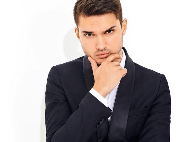 Portret van knappe mode stijlvolle zakenman model gekleed in elegant zwart klassiek pak. wat betreft zijn kin Gratis Foto