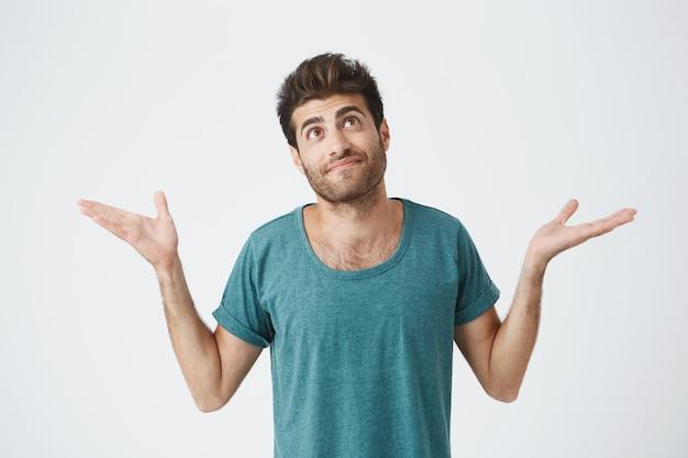 Portret van knappe spaanse man in blauwe doek, op zoek naar boven en schouderophalend laat zien dat hij niets kan doen met de situatie. gezichtsuitdrukkingen. Gratis Foto