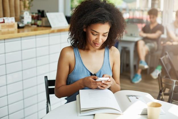 Portret van knappe vrolijke afrikaanse donkere student vrouw met donker krullend haar in blauw shirt zittend in café in de buurt van universiteit, academische samenvatting lezen, koffie drinken, chatten met vriendje o Gratis Foto