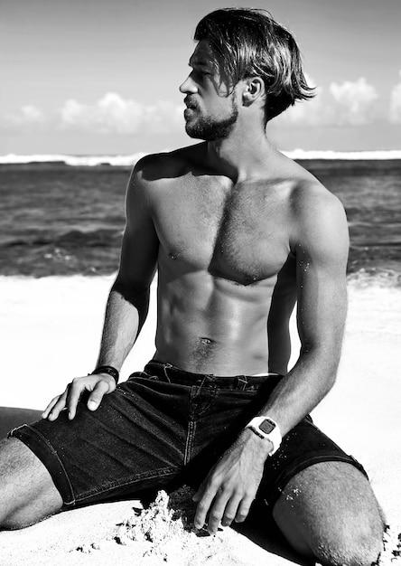 Portret van knappe zonnebaden mode man model poseren op zomer strand Gratis Foto