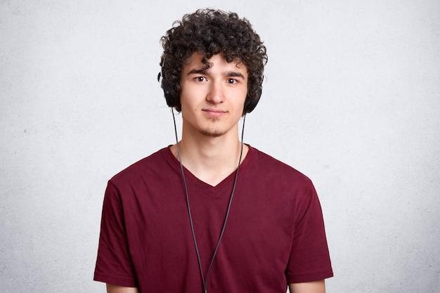 Portret van krullend hoofd man, gekleed in casual kastanjebruine t-shirt Gratis Foto