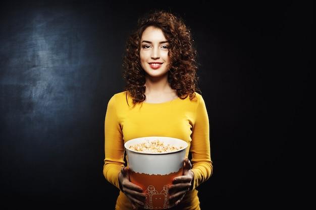 Portret van krullende de popcornemmer die van de vrouwenholding recht kijken Gratis Foto