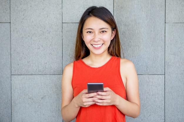 Portret van lachend aziatisch meisje met mobiele telefoon Gratis Foto