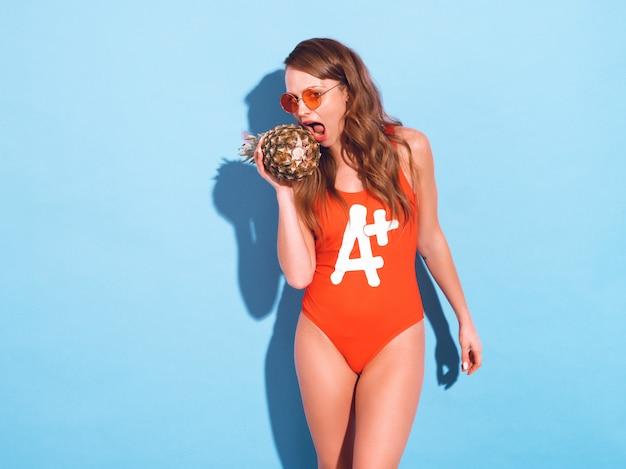 Portret van lachende brunette meisje in zomer rode badmode kleding en ronde zonnebril. sexy vrouw die verse ananas bijt. positief model poseren Gratis Foto