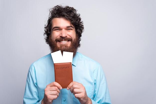 Portret van lachende gelukkig bebaarde man in casual bedrijf paspoort en vliegende kaartjes close-up Premium Foto