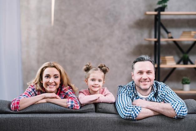 Portret van lachende jonge paar en dochter zittend op de bank Gratis Foto