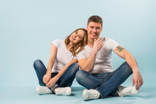 Portret van lachende jonge paar zittend op blauwe achtergrond Gratis Foto