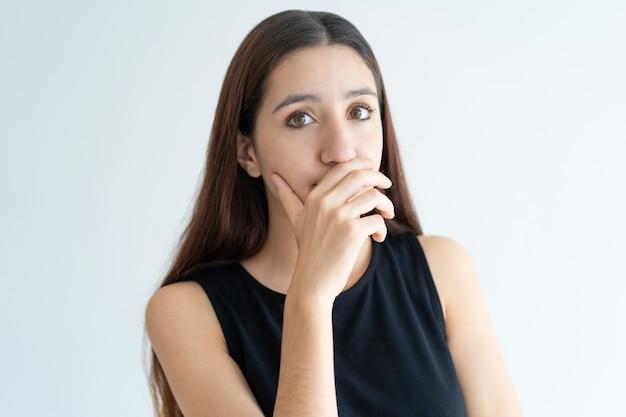 Portret van lachende jonge vrouw die mond behandelt met hand Gratis Foto