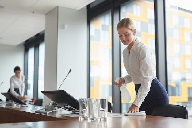 Portret van lachende jonge vrouw schoonmaaktafel met ontsmettingsspray in vergaderruimte tijdens de voorbereiding van een bedrijfsevenement in kantoor, Premium Foto