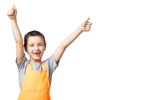 Portret van lachende jongen timmerman in oranje werk overall poseren, bedrijf, duimen omhoog Premium Foto