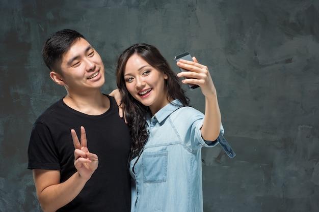 Portret van lachende koreaanse paar selfie foto maken op een grijze studio Gratis Foto