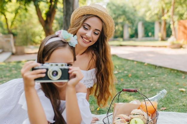 Portret van lachende langharige dame in hoed met de camera van de meisjesholding. buiten foto van jonge vrouw met plezier op picknick en haar dochter besie mand met maaltijd zitten. Gratis Foto