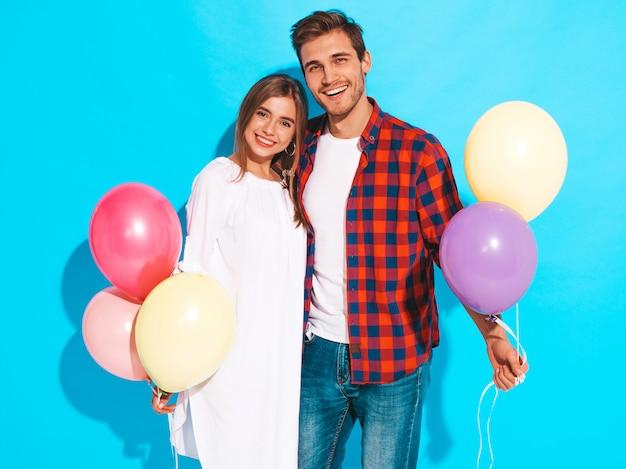 Portret van lachende mooi meisje en haar knappe vriendje bedrijf bos van kleurrijke ballonnen en lachen. fijne verjaardag Gratis Foto