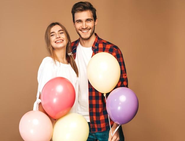 Portret van lachende mooi meisje en haar knappe vriendje bedrijf bos van kleurrijke ballonnen en lachen. gelukkige verliefde paar. fijne verjaardag Gratis Foto