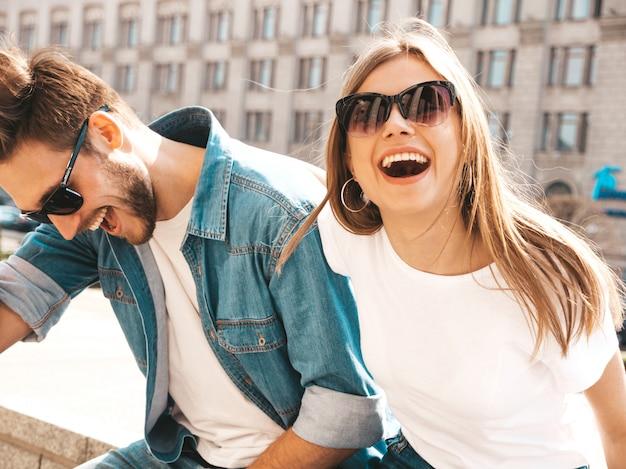 Portret van lachende mooi meisje en haar knappe vriendje in casual zomer kleding en zonnebril. . knuffelen Gratis Foto