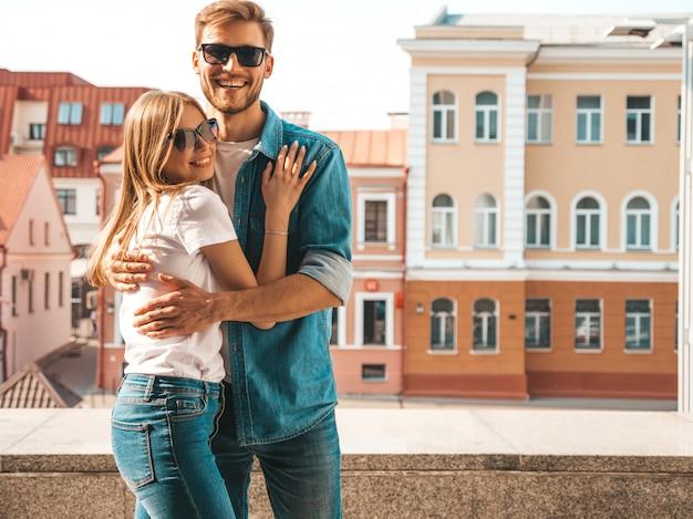 Portret van lachende mooi meisje en haar knappe vriendje in casual zomer kleding en zonnebril. Gratis Foto