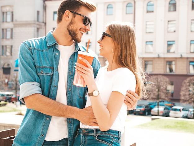 Portret van lachende mooi meisje en haar knappe vriendje in casual zomer kleding. . met fles water en stro Gratis Foto