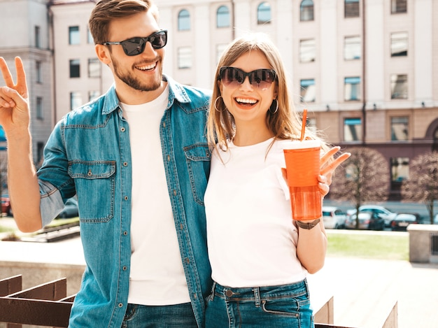 Portret van lachende mooi meisje en haar knappe vriendje in casual zomer kleding. . vrouw met fles water en stro Gratis Foto