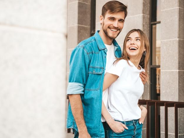 Portret van lachende mooi meisje en haar knappe vriendje. vrouw in casual zomer jeans kleding. . knuffelen Gratis Foto