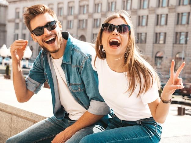 Portret van lachende mooi meisje en haar knappe vriendje. vrouw in casual zomer jeans kleding. . toont vredesteken Gratis Foto