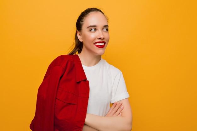 Portret van lachende mooie jonge dame met een gezonde huid, rode lippen en verzameld haar speels opzoeken op geïsoleerde muur, plaats voor tekst Gratis Foto