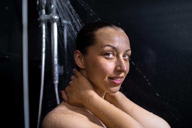 Portret van lachende naakte jonge vrouw die geniet van stromend water, douche neemt, staande in de badkamer, hand in hand op de nek, verzorgend op haar huid op zwarte muur Premium Foto