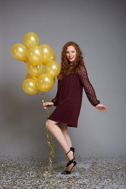 Portret van lachende vrouw met een heleboel ballonnen dansen Gratis Foto
