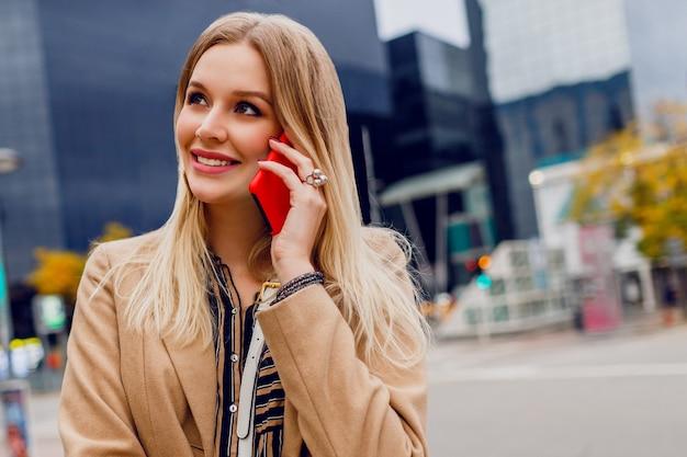 Portret van lachende vrouw praten via de mobiele telefoon close-up. succesvolle bedrijfsdame die smartphone gebruikt. stijlvolle accessoires. beige jas. stedelijke gebouwen Gratis Foto